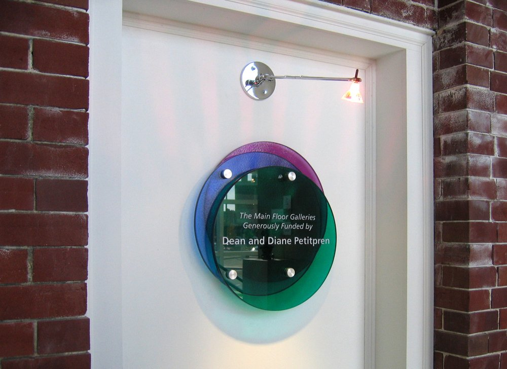 Etched & Tinted Glass Plaque: Donor names are etched into top panel of a series of glass panels. The colors are circle design them are consistent with the atrium donor wall.