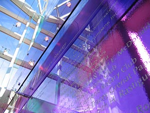 Donor wall with cascading sheets of glass. Donor names are etched into the tinted glass, allowing natural light to shine through.