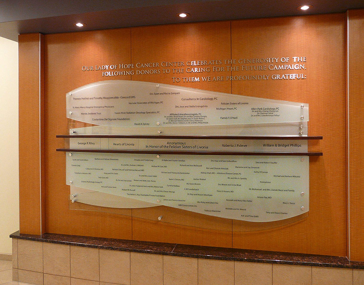 Donor names are permanently etched into glass panels. Individual metal letters provide campaign information.